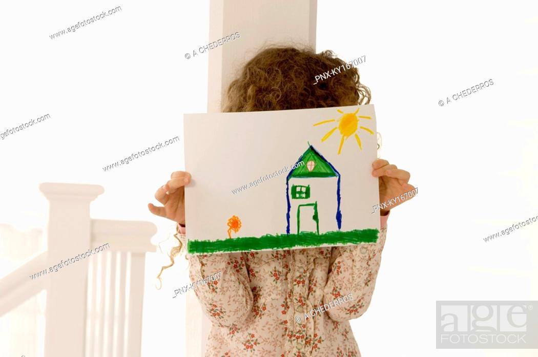 Stock Photo: Girl holding a drawing sheet in front of her face.