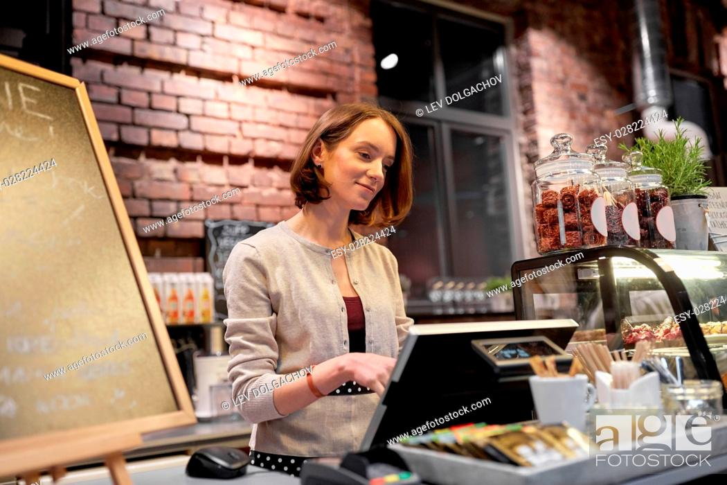 Stock Photo: small business, people and service concept - happy woman or barmaid at counter with cashbox working in cafe or coffee shop.