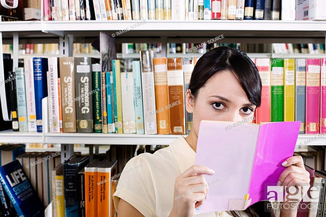Stock Photo: Young woman in library with book.