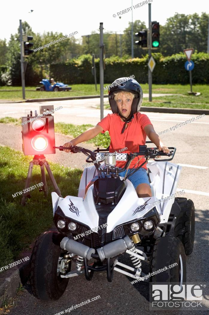 Stock Photo: Boy with quadbike on driver training area with speed trap.