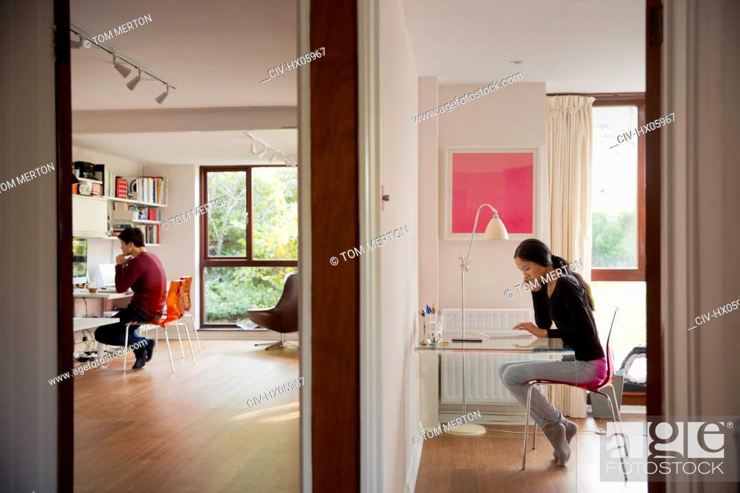 Stock Photo: Couple working in bedroom and home office.