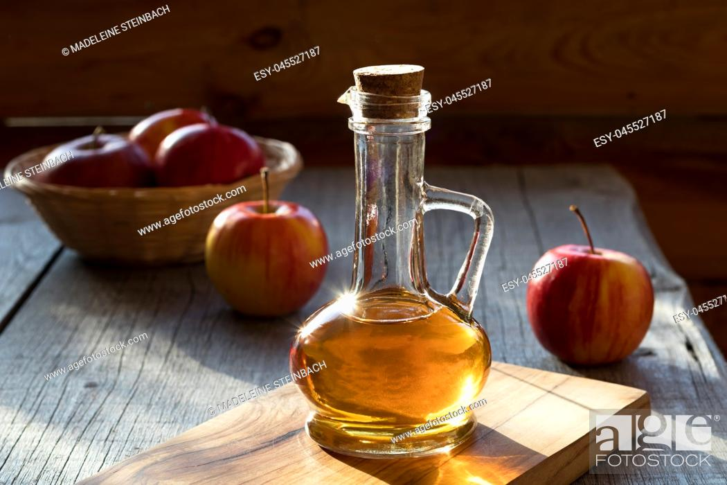 Stock Photo: A bottle of apple cider vinegar in the morning sun, with apples in the background.