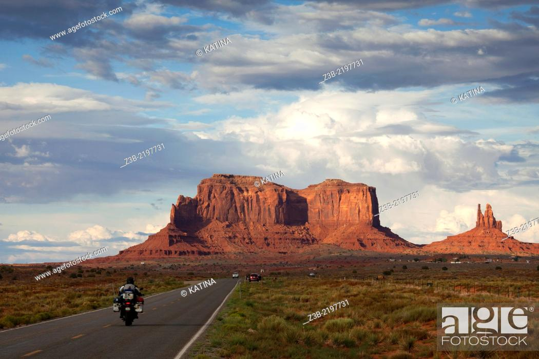 Stock Photo: Motorcycle driving towards buttes in Monument Valley, Utah, USA.