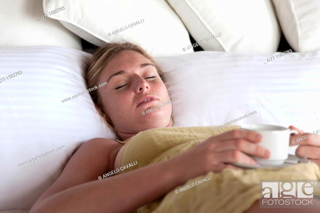 Stock Photo: Maldives Islands Ari Atoll Woman in bed with a cup of coffee.