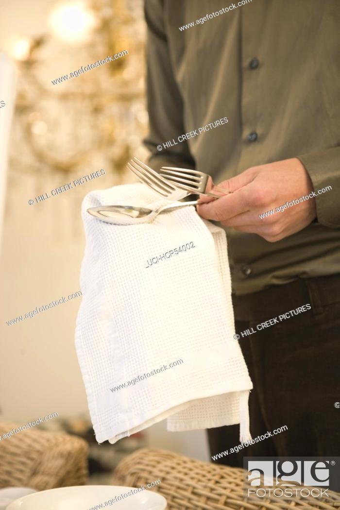 Stock Photo: Man polishing silver cutlery.