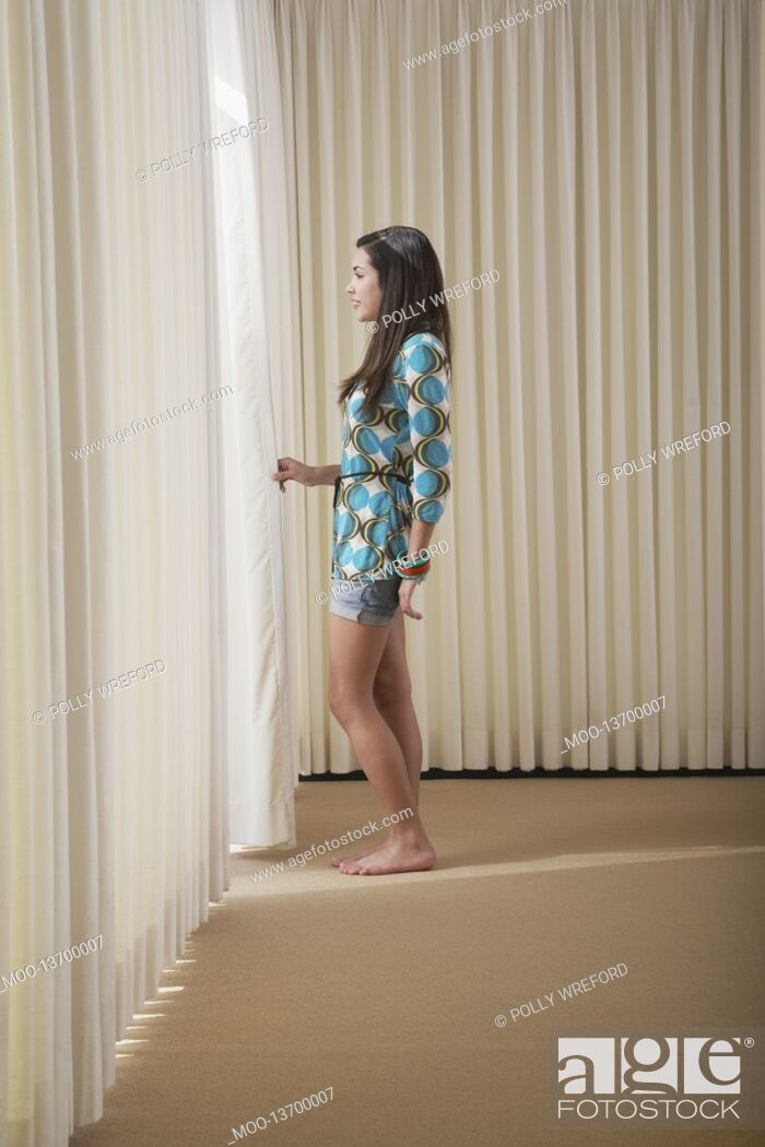 Stock Photo: Teenage girl 16-18 standing in empty room drawing aside blinds side view.