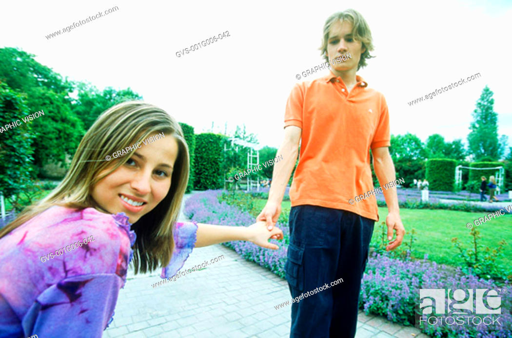 Stock Photo: Young couple holding hands in a garden.