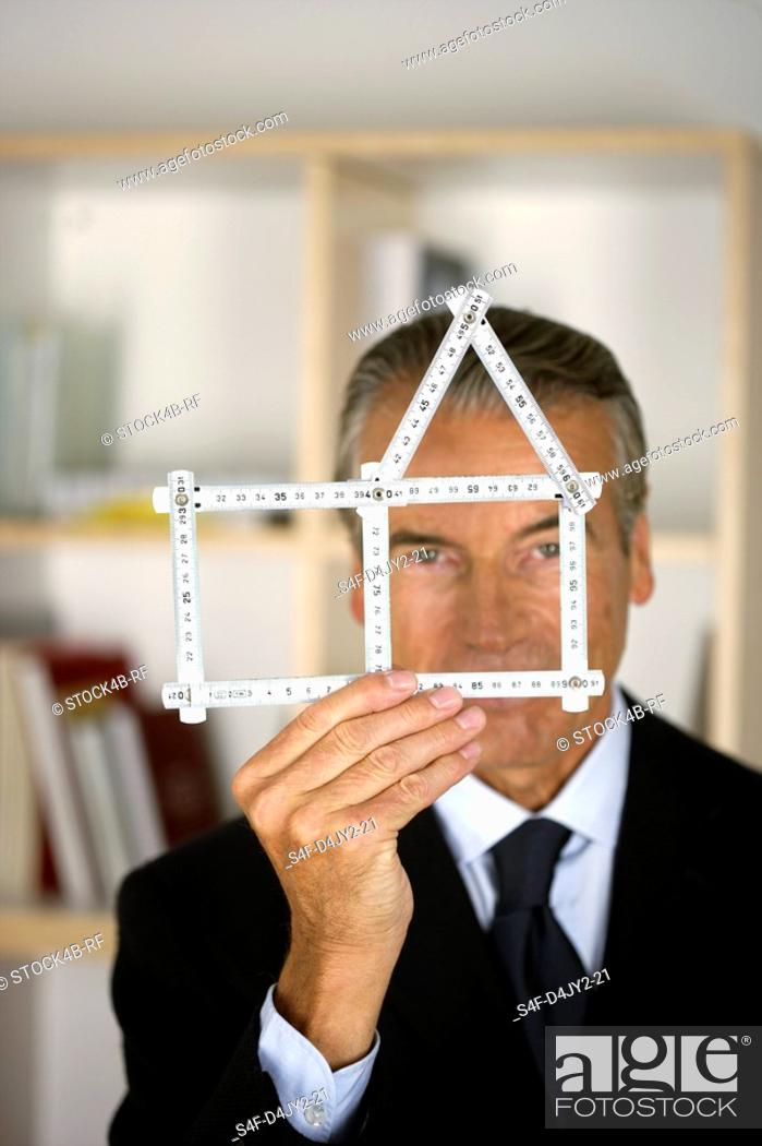 Stock Photo: Senior businessman holding a model of a house.