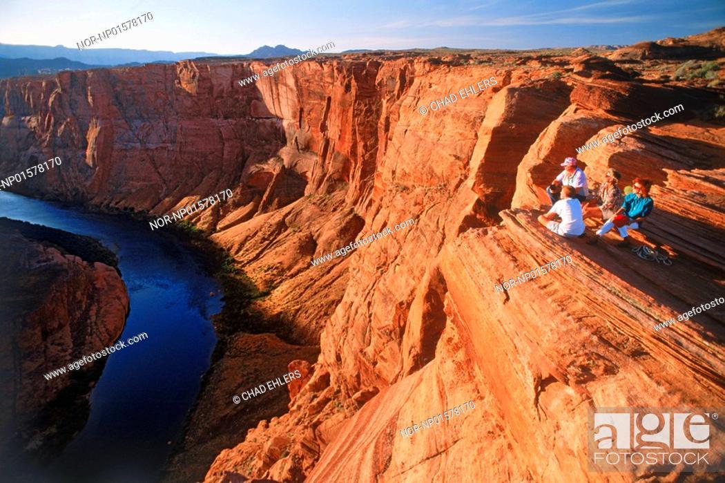 Stock Photo: USA, Arizona - People sitting on rocky cliff at Glen Canyon.