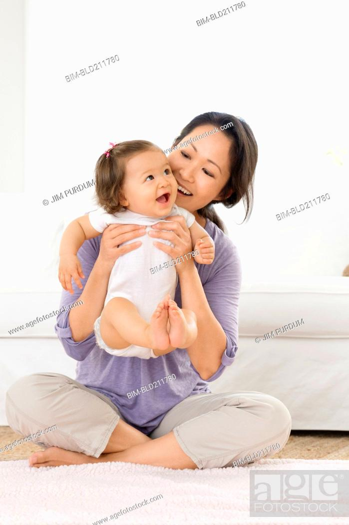 Stock Photo: Mother playing with baby girl in living room.