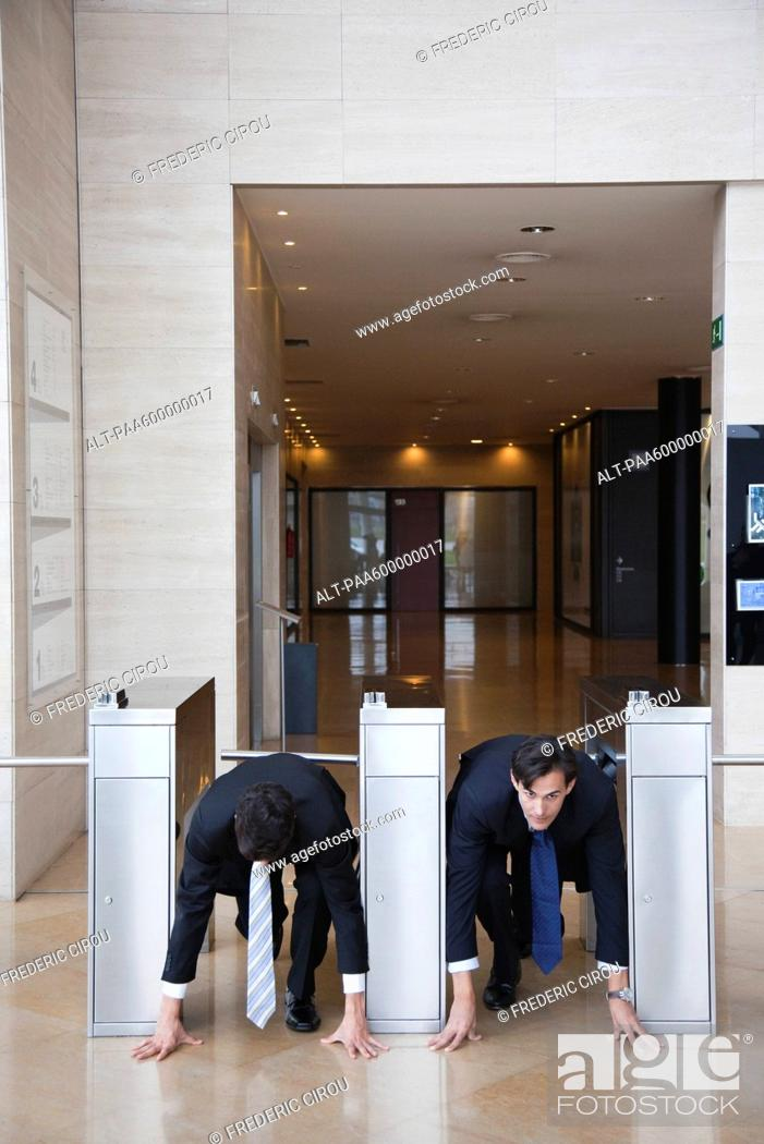 Stock Photo: Businessmen crouching in starting position in lobby turnstiles.