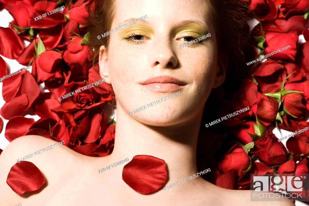 Stock Photo: beauty woman on roses patals.