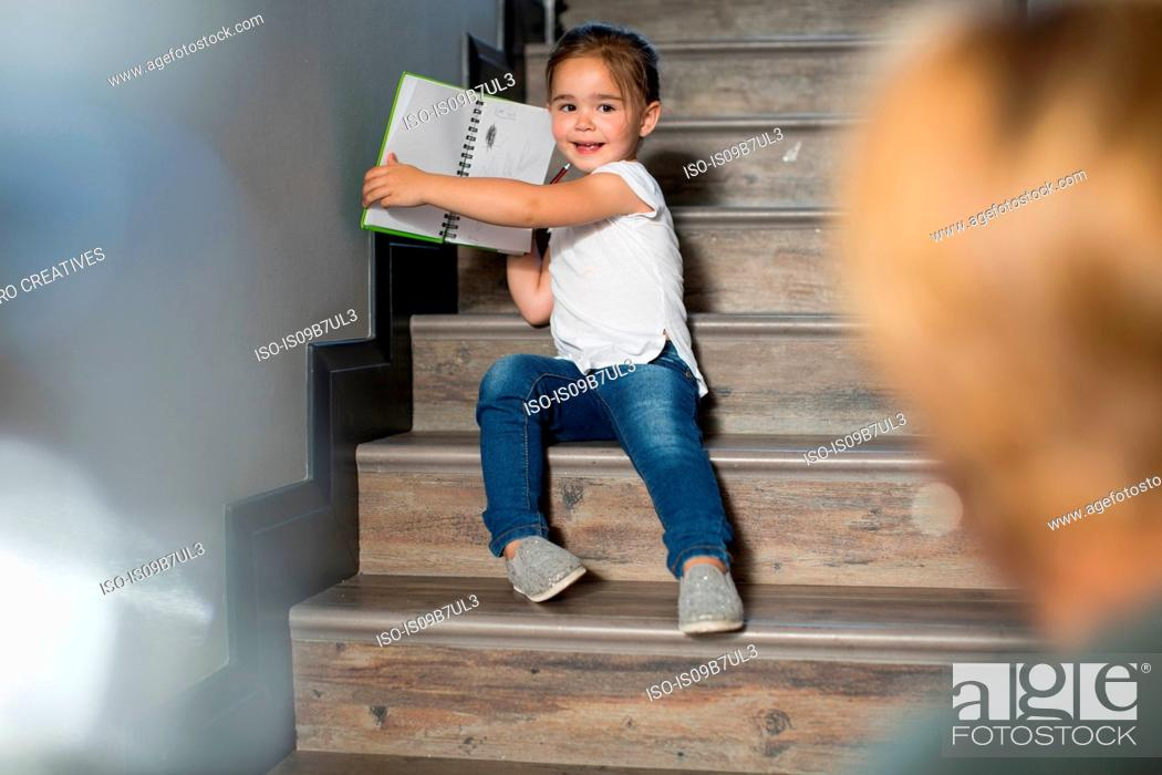 Stock Photo: Girl on stairs proudly showing mother pencil drawings.