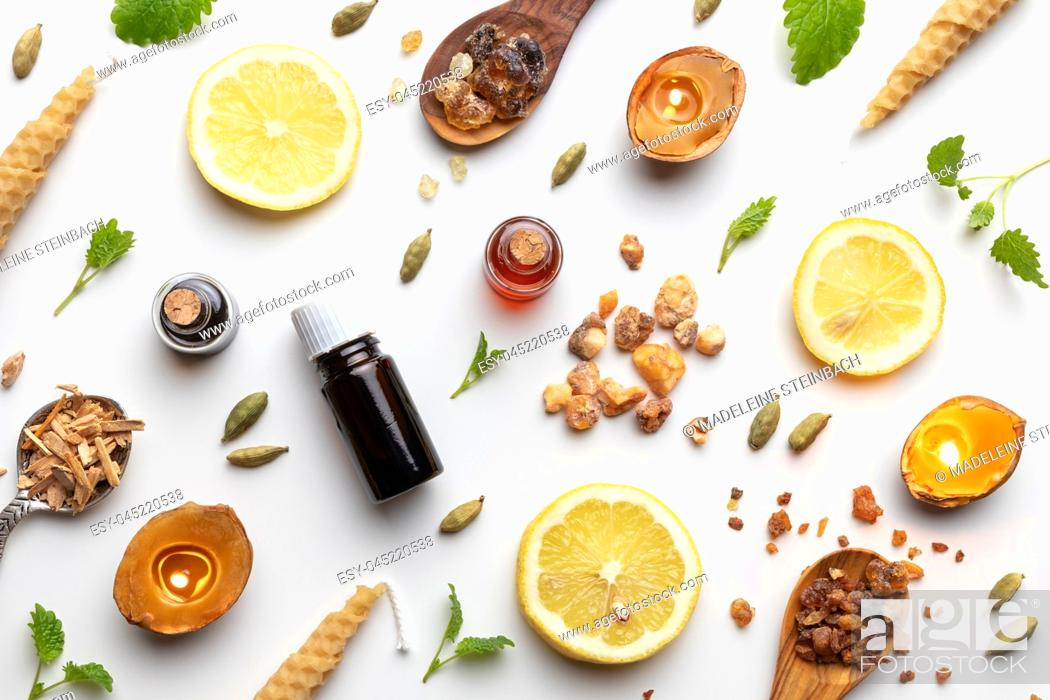 Stock Photo: Bottles of essential oil with frankincense, cardamon, melissa, fresh lemon and other ingredients on a white background.
