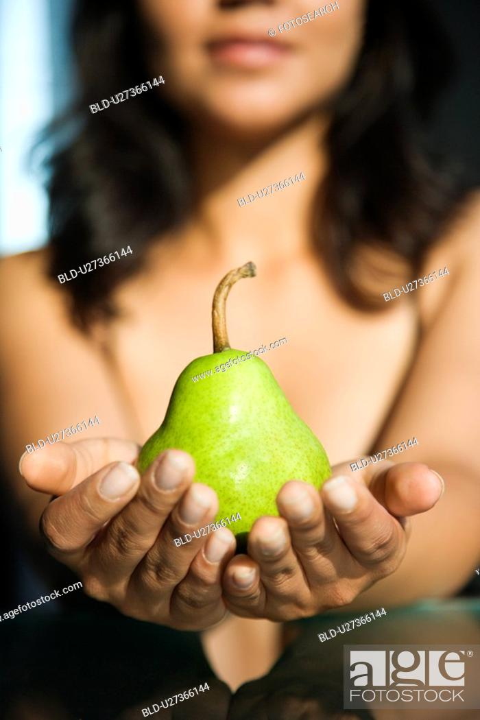 Stock Photo: Woman holding pear in outstretched hands toward viewer.