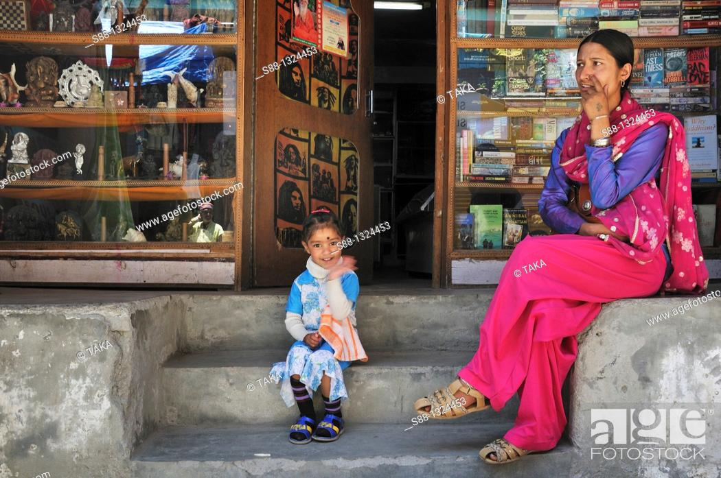 Stock Photo: Mother and daughter sitting in front of the book shop in New Manali. Manali, Himachal Pradesh, India.