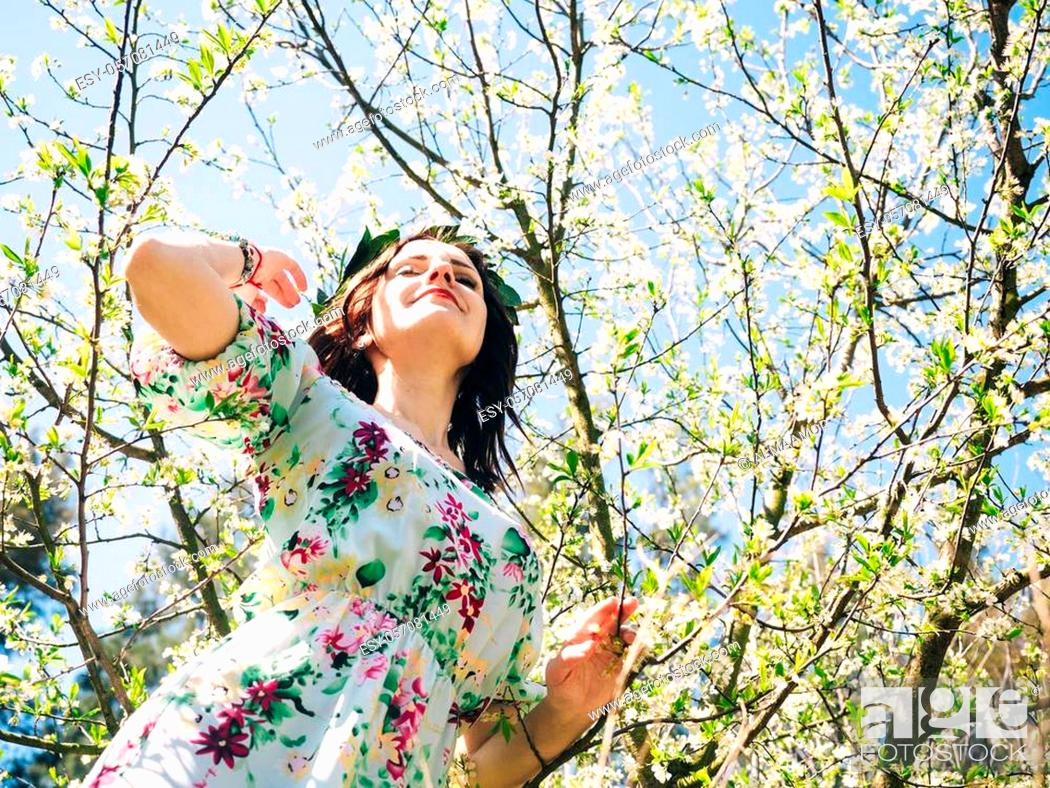 Stock Photo: Young beautiful woman in bay leaf wreath dreaming with closed eyes in spring blossom cherry garden.