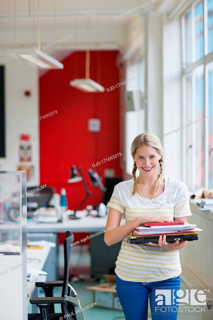 Stock Photo: Smiling woman carrying laptop and paperwork in office.