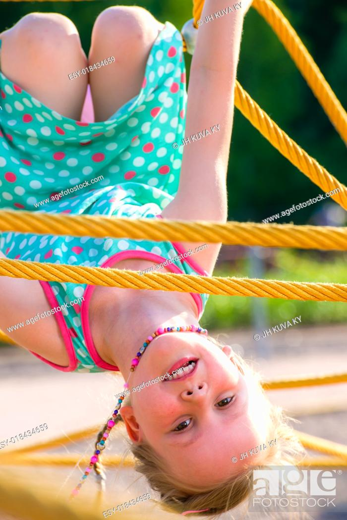 Stock Photo: Young girl on the jungle gym, sunny day.