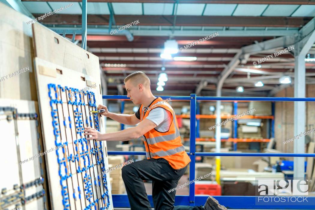 Stock Photo: Worker checking cardboard cutter in cardboard box factory.
