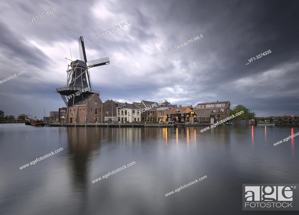 Imagen: View of Windmill De Adriaan reflected in the canal of the river Spaarne during golden storm, Haarlem, Amsterdam district, Papentorenvest, Randstad.