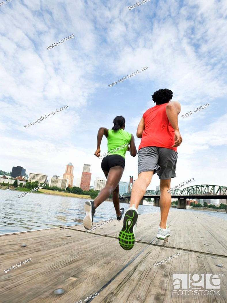 Stock Photo: Couple running on urban boardwalk along river.