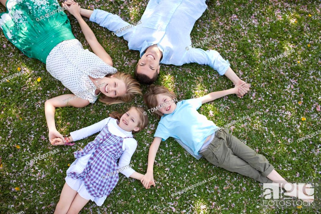 Stock Photo: Family laying in grass together.