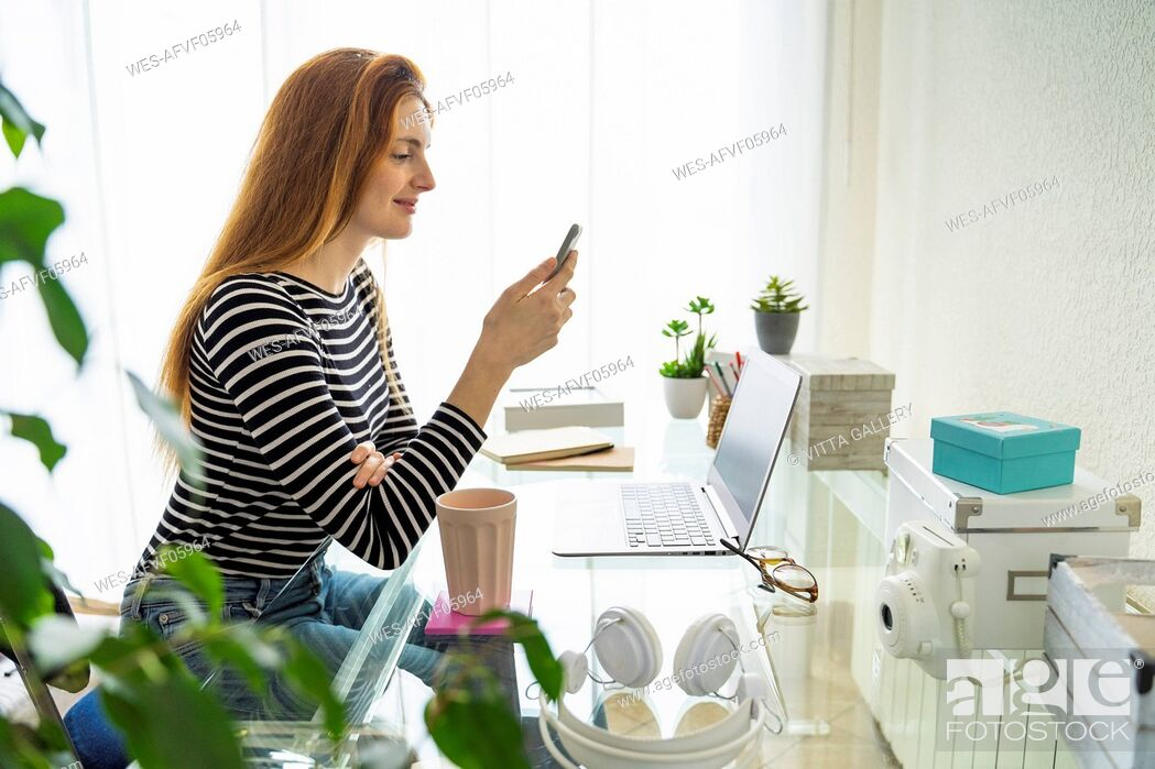 Stock Photo: Young woman using smartphone at desk at home.