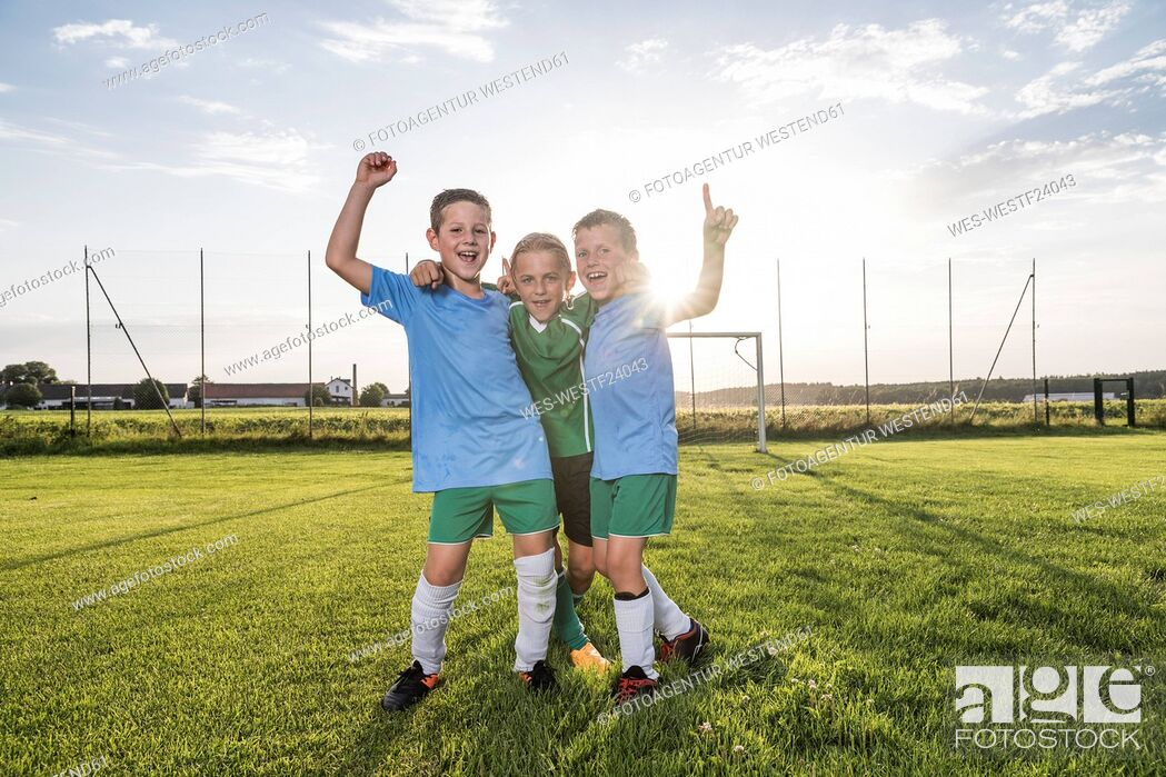 Stock Photo: Young football players cheering on football ground.