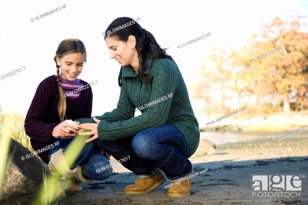 Stock Photo: Mid adult woman examining her daughter.