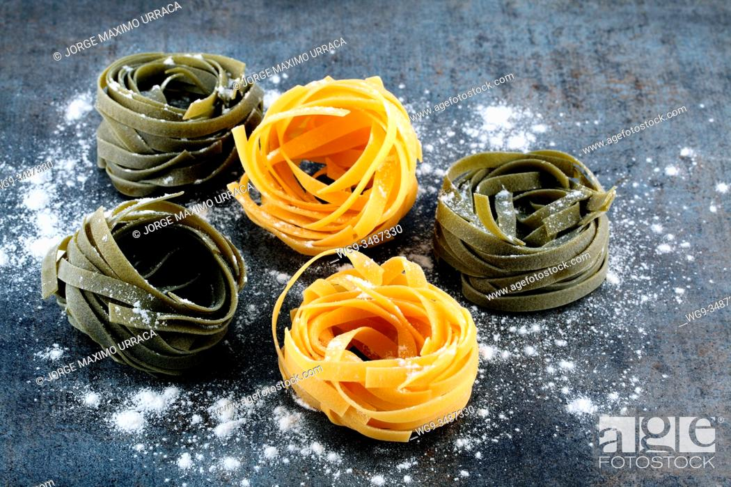 Stock Photo: Tagliatelle pasta for cooking on artistic background.
