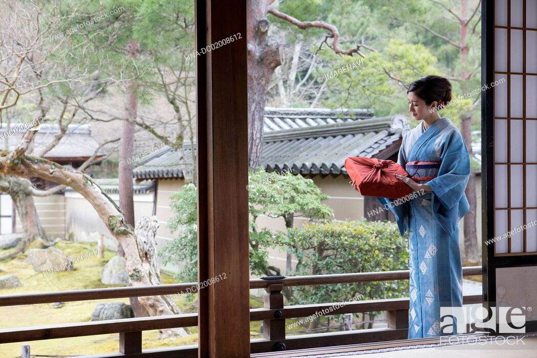 Stock Photo: Young Japanese woman in kimono with parcel.