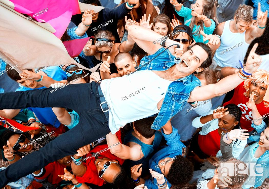 Stock Photo: Performer singing and crowd surfing at music festival.