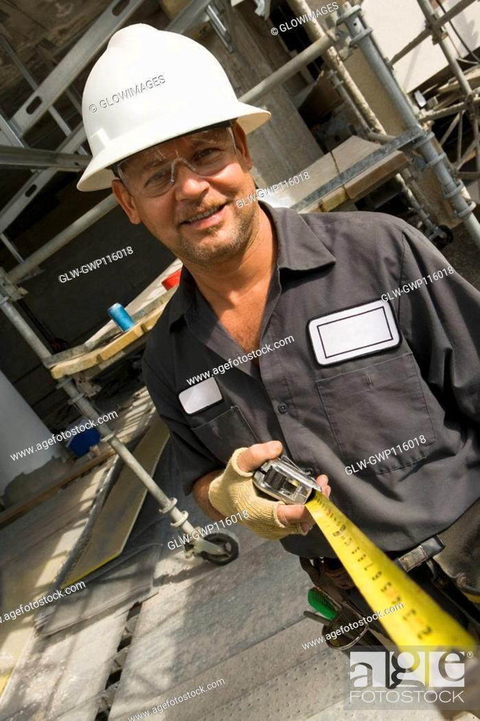 Stock Photo: Portrait of a male construction worker holding a tape measure and smiling.