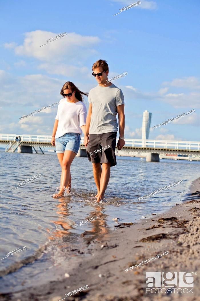 Stock Photo: Full length of happy young couple holding hands while walking in sea.