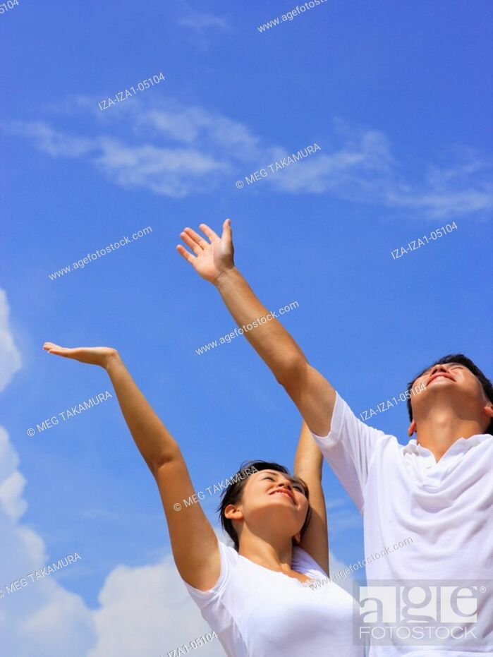 Imagen: Low angle view of a mid adult couple smiling with their arms raised.