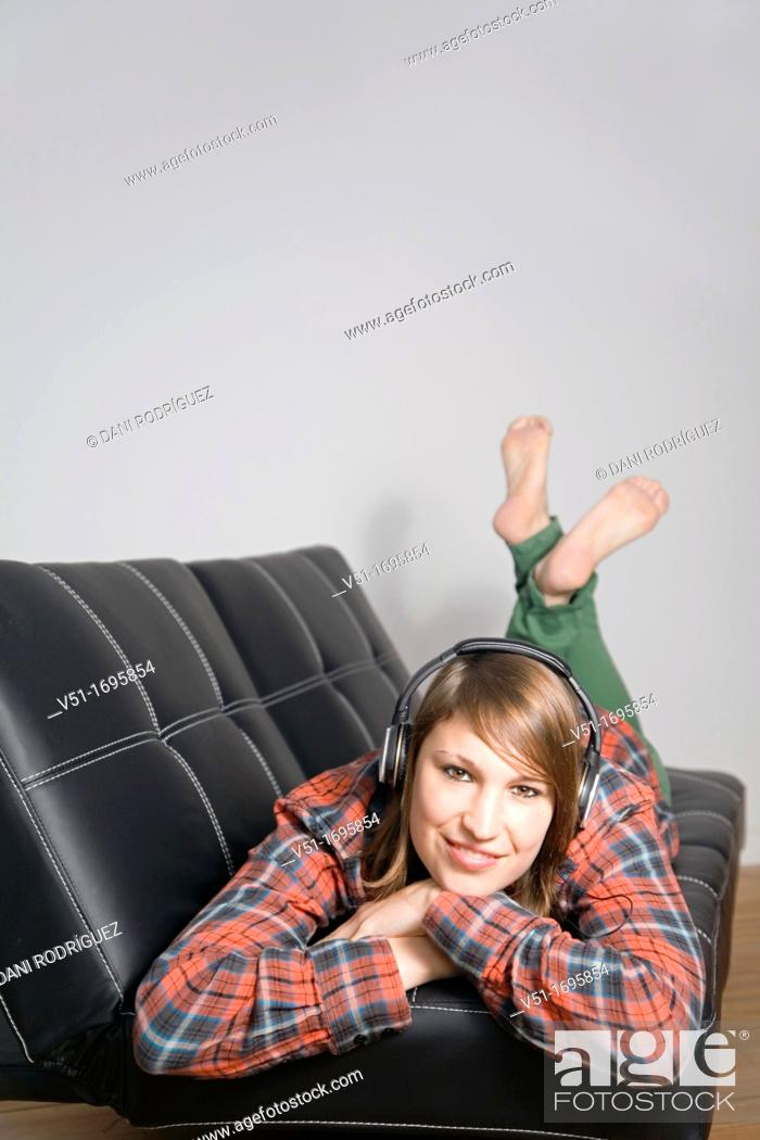 Stock Photo: Young woman listening to music on the couch smiling at camera.