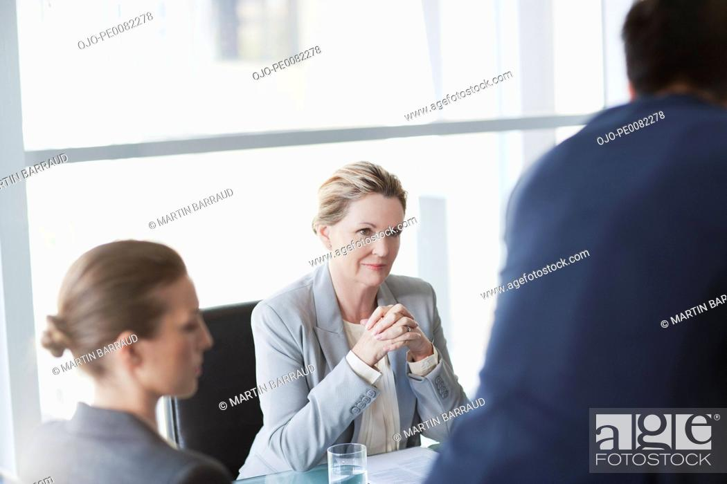 Stock Photo: Businesswoman with hands clasped in meeting.