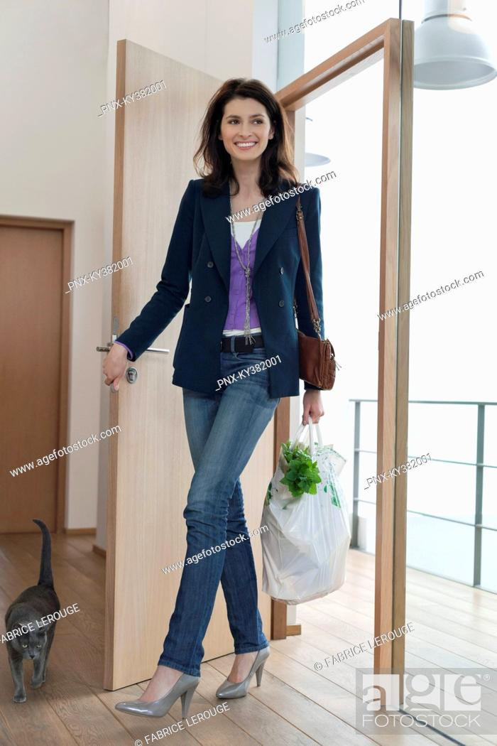 Stock Photo: Woman arriving home with a bag of groceries.