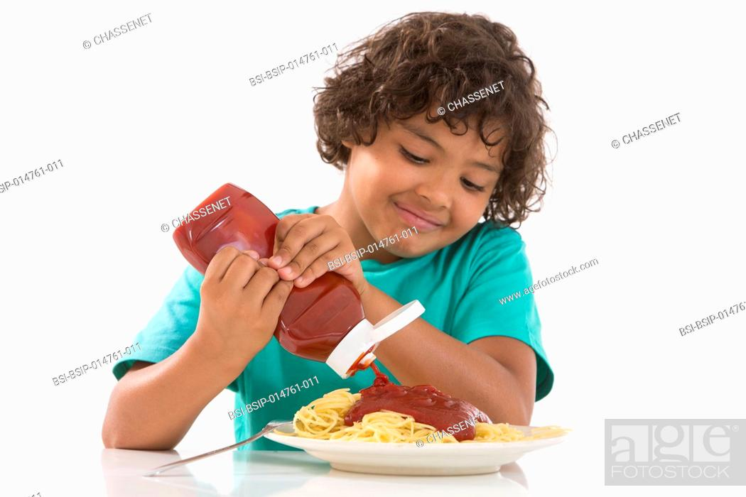 Stock Photo: Boy eating spaghetti with ketchup.