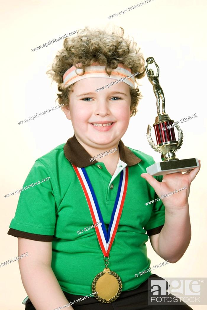 Stock Photo: Portrait of a boy holding a trophy.