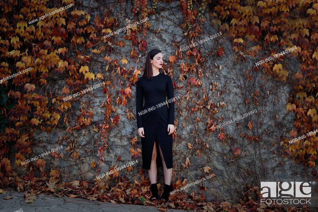 Stock Photo: Beautiful young woman, model of fashion, on wall full of autumn leaves, with eyes closed. Fine art photograph.
