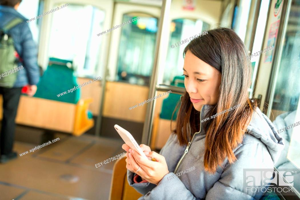 Stock Photo: Woman using cellphone inside train compartment at Japan.