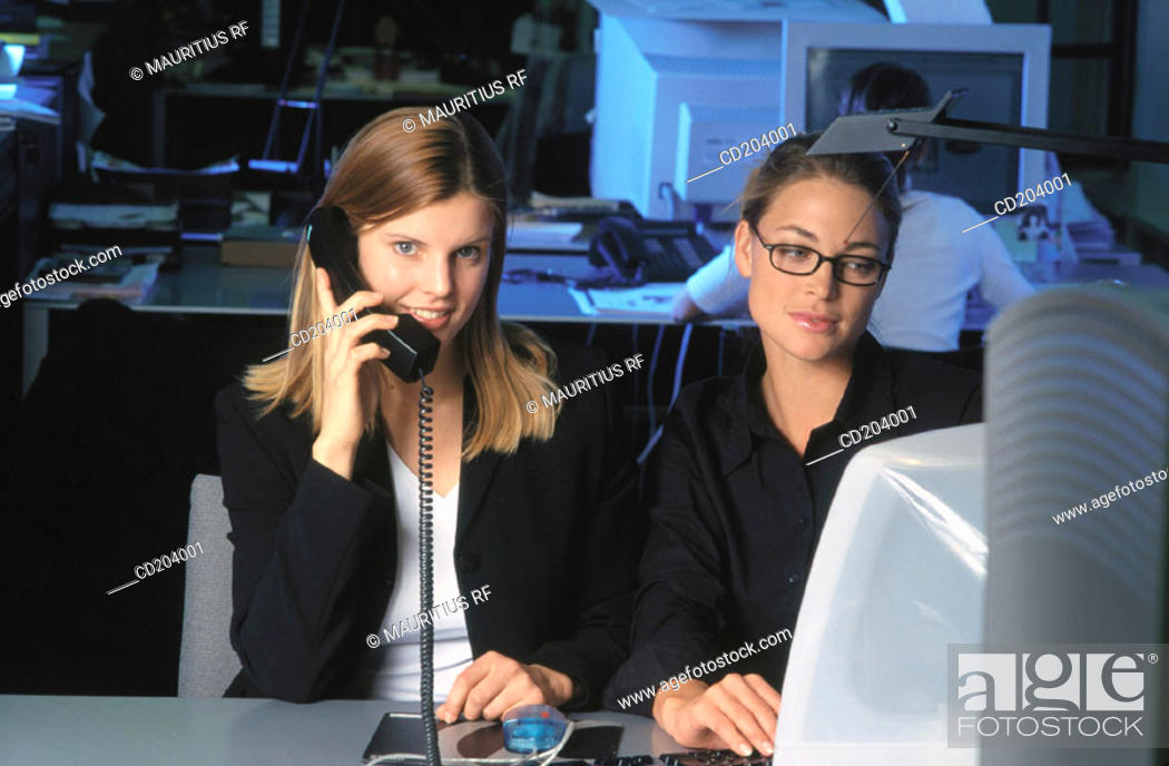 Stock Photo: Two businesswomen in front of computer, businesswoman talking on phone.