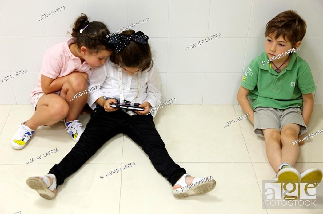 Stock Photo: Children using a portable console, AZTI-Tecnalia Marine and Food Research Center, Derio, Bizkaia, Euskadi, Spain.