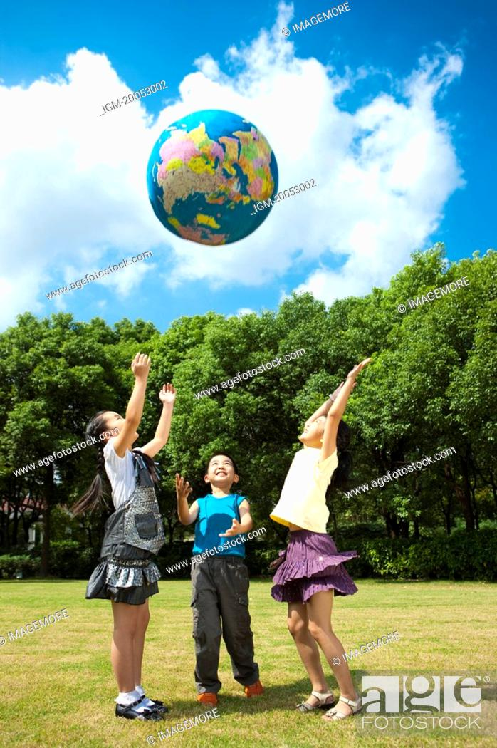 Stock Photo: Three children standing on the lawn and playing with globe together.