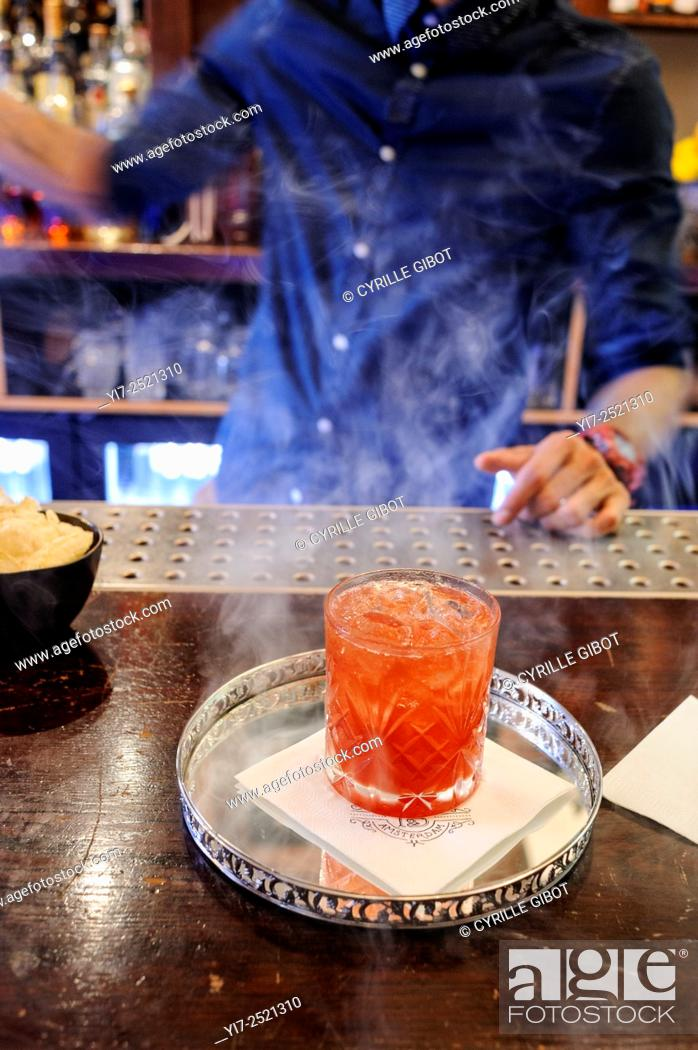 Stock Photo: Bartender serving a cocktail called Smoke and Mirrors, Tales and Spirits bar, Amsterdam, Netherlands, Europe.