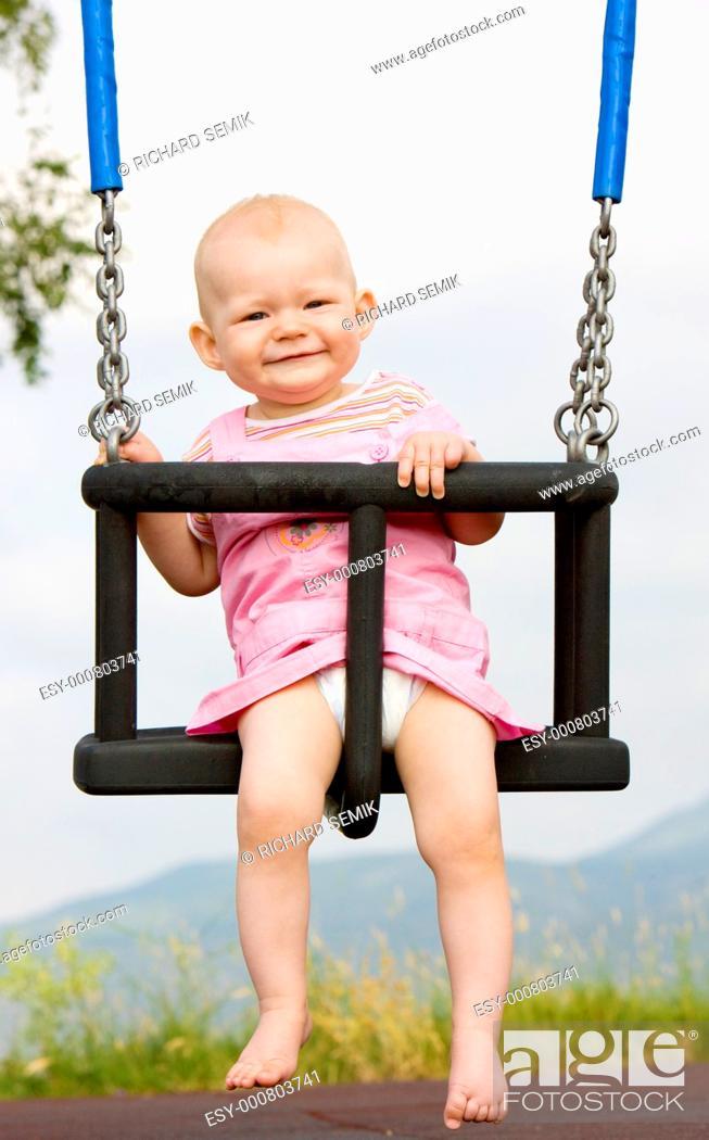 Stock Photo: baby girl sitting on swing.