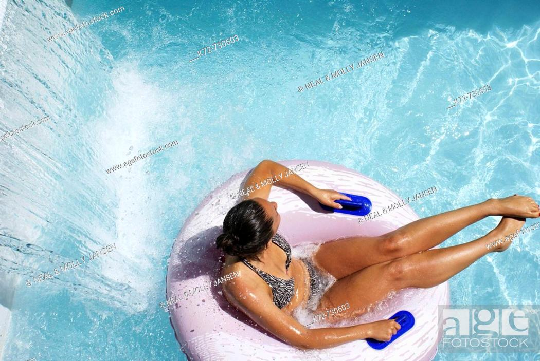 Stock Photo: Lazily floating by a waterfall at the waterpark adds to the cooling effect on a hot summer day.
