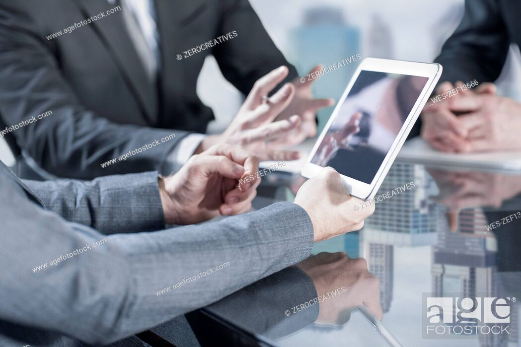Stock Photo: Businesspeople using tablet in meeting.